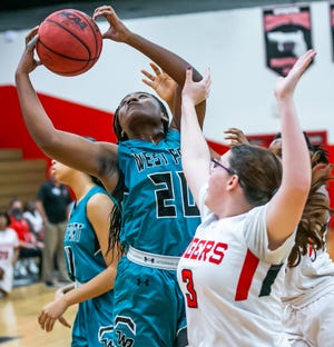 West Port's Nya Brigham grabs a rebound away from Dunnellon's Paige Powell. The Wolf Pack defeated the Tigers, 75-28, Friday night.