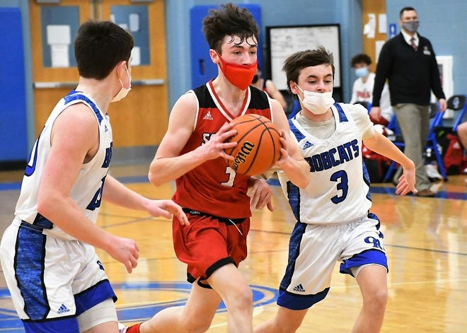 Spaulding's Nick Morin, center, drives to the basket on Oyster River's Hayden Marshall, left, and Connor Shea during action Friday in Durham.