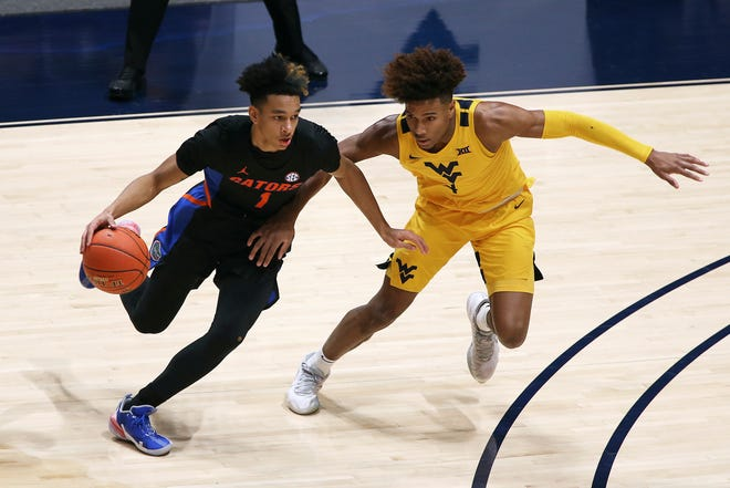 Florida guard Tre Mann is defended by West Virginia guard Miles McBride during the first half Saturday in Morgantown, W.Va.