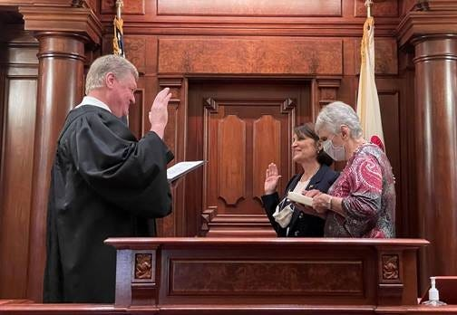 Sally Turner, center, is sworn into the Illinois Senate on Saturday by her husband, Appellate Judge John Turner. At right is the senator's mother.