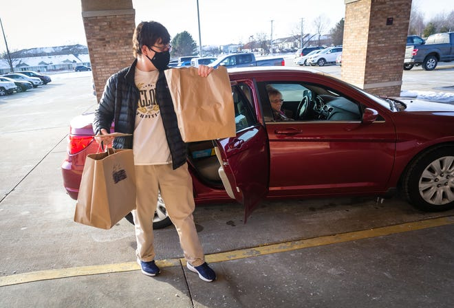 Sacred Heart-Griffin senior John Schmidt helps unload a donation of food through the drive-thru setup for the 14th annual All-City Food Drive to benefit the St. Martin de Porres Center at the Knights of Columbus Hall in Springfield, Ill., Friday, January 29, 2021. Students from Lanphier, Southeast, Springfield and Sacred Heart-Griffin high schools were on site to help collect monetary and food donations. The All-City Food Drive is normally held in conjunction with the Boys City Basketball Tournament, but due to the COVID-19 pandemic canceling the event, the Knights of Columbus stepped up to help host this yearÕs fundraiser, with donations topping $100,000. [Justin L. Fowler/The State Journal-Register]