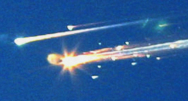 In this Feb. 1, 2003 photo, debris from the space shuttle Columbia streaks across the sky over Tyler, Texas.