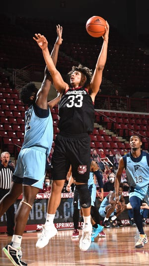 UMass forward Tre Mitchell (33) goes up for a shot against Rhode Island. Mitchell, who starred at Woodstock Academy, has been nominated for the Karl Malone Award by the Basketball Hall of Fame. You can vote at hoophallawards.com.
