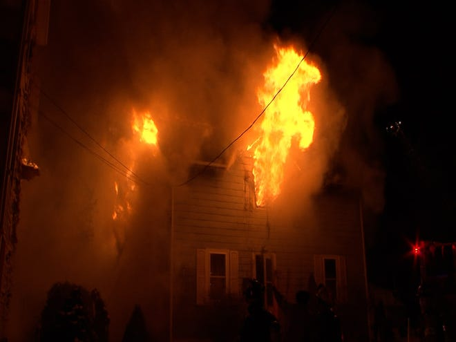 Flames shoot through a second floor window of a home on 16 Auclair St. in Blackstone early Saturday morning.