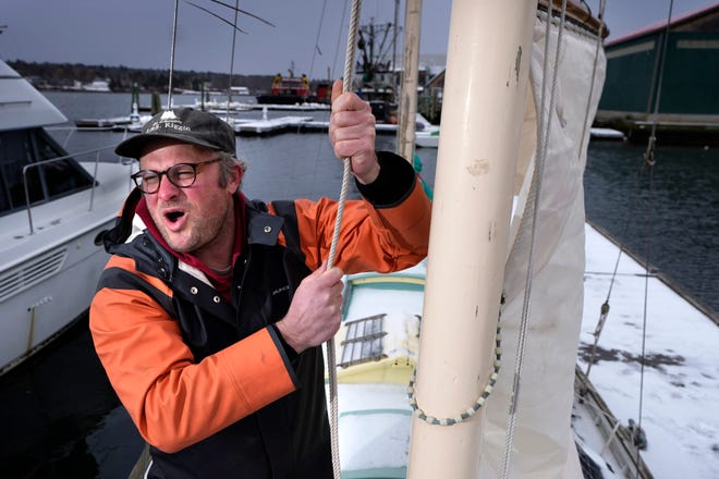 Bennett Konesni sings a sea shanty while raising a sail on his ketch Thursday in Belfast, Maine.