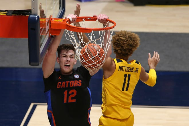 Florida forward Colin Castleton dunks on West Virginia forward Emmitt Matthews Jr. (11) during the second half Saturday in Morgantown, W.Va.