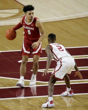Alabama's Jaden Shackelford (5) goes against Oklahoma's Umoja Gibson (2) during the first half of an NCAA college basketball game in Norman, Okla., Saturday, Jan. 30, 2021. (AP Photo/Garett Fisbeck)