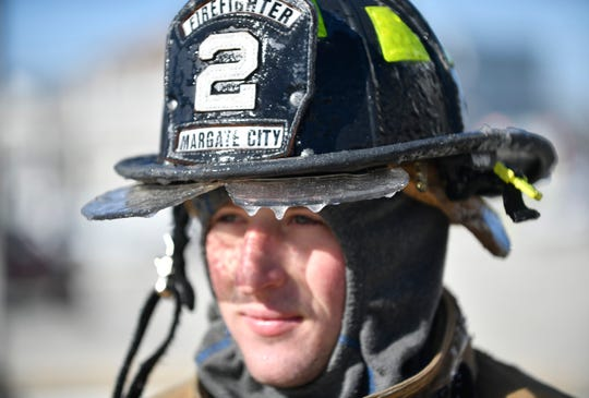 Ice forms on the helmet of Margate City firefighter Chris Fantazzia during a blaze on Ocean City's boardwalk on Saturday morning, Jan. 30, 2021.