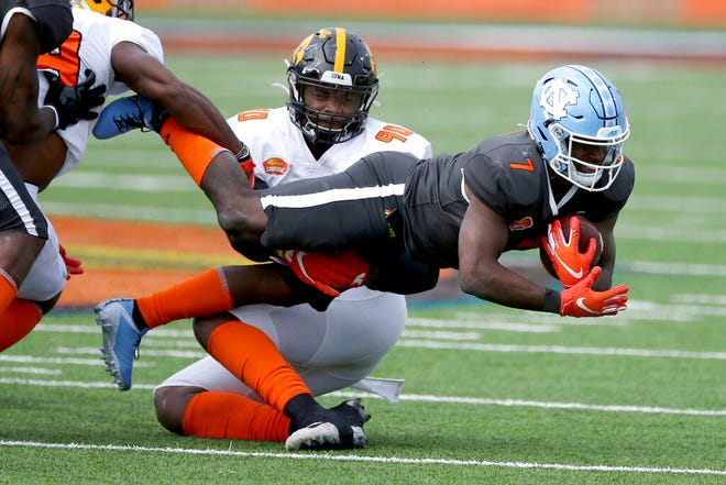 National Team running back Michael Carter of North Carolina (7) is tackled by American Team linebacker Jabril Cox of LSU (19) and American Team defensive lineman Chauncey Golston of Iowa (90) Saturday during the Senior Bowl in Mobile, Ala.