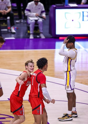 Guard Mac McClung (0) cheers on guard Terrence Shannon, Jr. (1) for scoring a basket that helped No. 10 Texas Tech defeat LSU 76-71 in a SEC/Big 12 Challenge game Saturday at the Pete Maravich Assembly Center. McClung and Shannon combined for 45 points. [Stephen Lew/USA TODAY Sports]