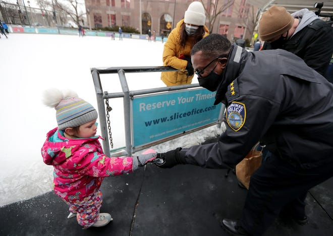 Emilia Knezic, 2, is handed a puck by Acting Milwaukee Police Chief  Jeffrey Norman during the Milwaukee Police Department community event at Red Arrow Park Ice Skating Rink on North Water Street Saturday, Jan. 30, 2021, in Milwaukee.
