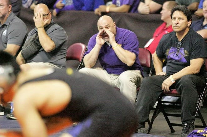 Mesa boys wrestling head coach David DiDomenico (middle, seated) gives instructions to his team member during a match.