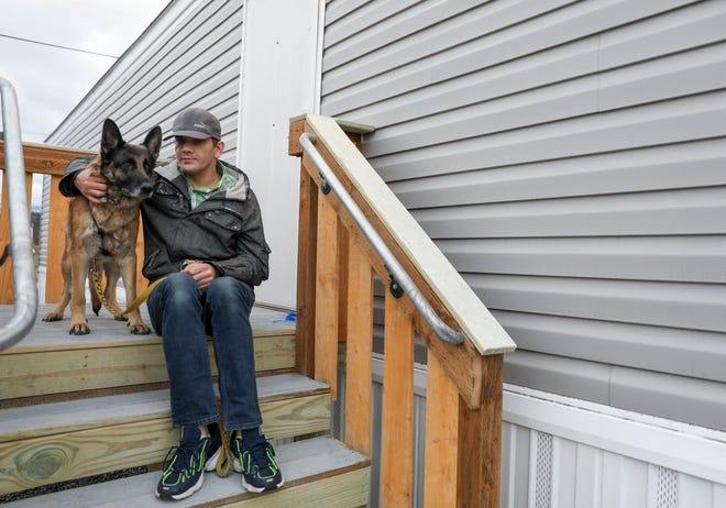 Nick Schumacher and his dog Charlie prepare to move into a trailer provided by FEMA after losing his home to the Santiam Canyon wildfires, after living in hotels for several months.