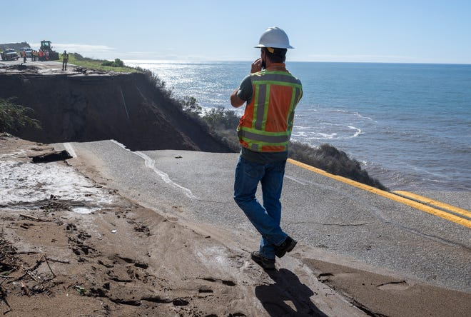 A California Department of Transportation employee walks toward the gaping hole in U.S. Highway 1 on Friday, Jan. 29, 2021.