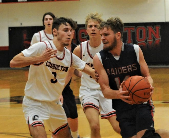 Morgan's Carver Myers tries to drive past Coshocton's Nathan Fauver in Friday's contest at The Wigwam. The Raiders won 44-33.