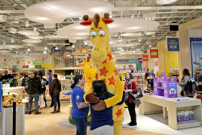A girl hugs the Toys R Us mascot, Geoffrey, at the new store at a mall in Paramus, N.J. in this Dec. 9, 2019 file photo