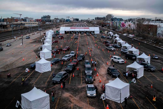 People arrive for COVID-19 vaccination at a drive through setup at Coors Field baseball stadium on January 30, 2021, in Denver, Colorado.