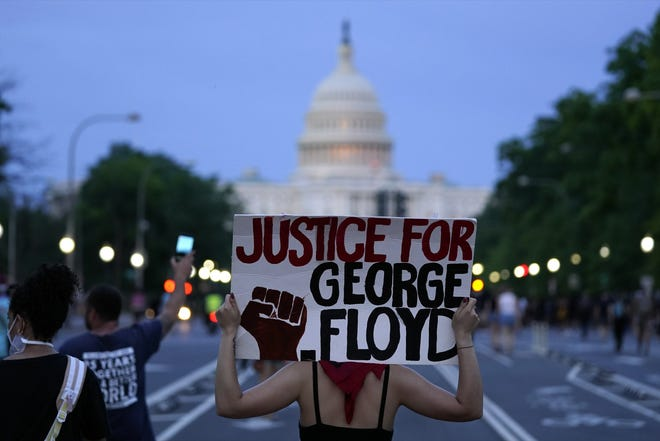 In this May 29, 2020, photo, demonstrators walk along Pennsylvania Avenue in Washington, D.C. as they protest the death of George Floyd, a black man who died in police custody in Minneapolis. [AP Photo/Evan Vucci]