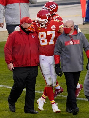 Kansas City tight end Travis Kelce (87) walks off the field with coach Andy Reid after a divisional round game against the Browns. Both Reid and Tampa Bay Buccaneers coach Bruce Arians are considered players' coaches, though they do it in different ways.