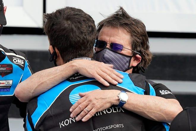 O dono da equipe Wayne Taylor, certo, abraça seu filho Ricky após vencer o Rolex 24 em Daytona no domingo.