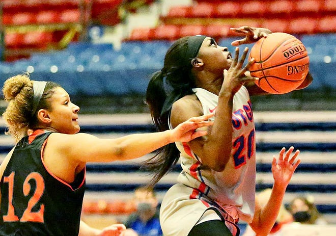 Hutchinson Community College's Lojong Gore (20) is fouled on her drive to the basket by Neosho County's Tanay Williams (12) during their game Saturday night at the Sports Arena. Gore scored 14 points in the game.