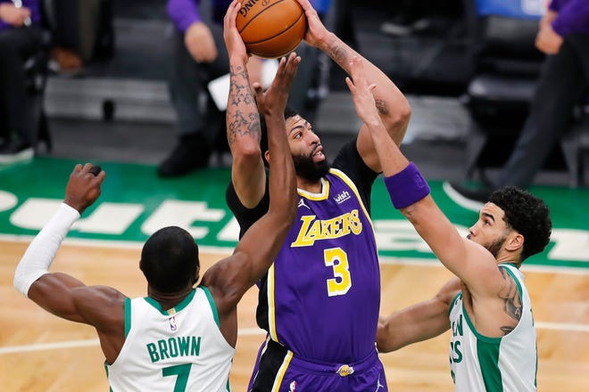 Lakers center Anthony Davis (middle) shoots between Celtics forwards Jaylen Brown (left) and Jayson Tatum during the first half of Boston's 96-95 loss to Los Angeles Saturday night in Boston.