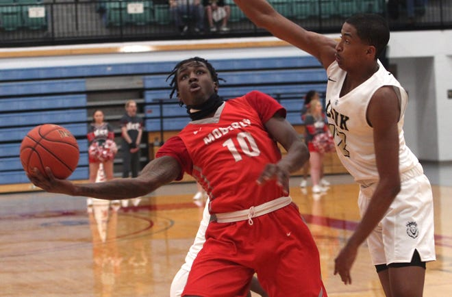 Moberly Greyhounds returning sophomore Cortez Mosely puts up an acrobatic shot around Link Year Prep's Teafale Lenard during Saturday night's 93-2 loss to the Lions from Branson. Mosely scored 22 points in a losing effort.