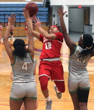 Moberly Area Community College sophomore Bi'Anna Pettis splits the seams of Spoon River College's Jai'Renee McCoy (#4) and T'Alla Brown as she attacks the rim and draws a foul Saturday. Pettis made three free throws to help the Lady Greyhounds earn a104-57 home victory at the Orscheln Industries Classic.