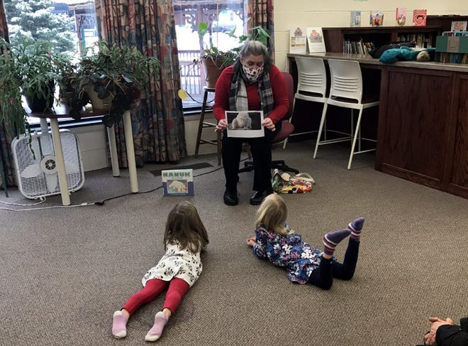Earlville Free Library director Shari Taylor reads a story to Ella Babcock and Sadie Pinney recently at the library. It's Library Lovers Month there throughout February.