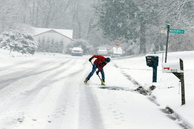 David Rigby shovels his driveway during a snowstorm Sunday in Mechanicsville, Virginia. Forecasters say the massive storm has triggered winter storm warnings all along the East Coast.