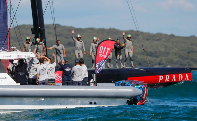 Crew members from Italy's Luna Rossa, background, wave to the crew from American Magic on Saturday following the America's Cup challenger series semifinal near Auckland, New Zealand.
