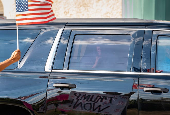 Former President Donald Trump passes supporters while traveling in his motorcade in West Palm Beach, Fla., on Wednesday, en route to Mar-a-Lago in Palm Beach.