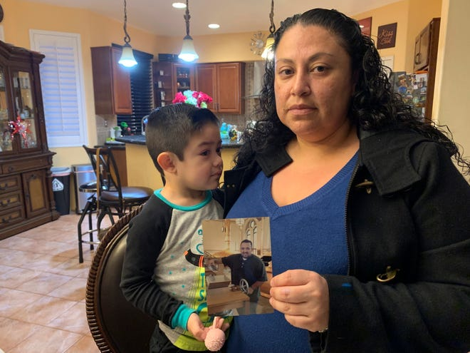 Nancy Espinoza, 37, sits with her 3-year-old son at their home in Corona while holding a photo of her husband, Antonio Espinoza, who died of COVID-19 three days earlier. Espinoza said she never imagined the virus would take the life of her 36-year-old husband, who managed a hospice nurse program.
