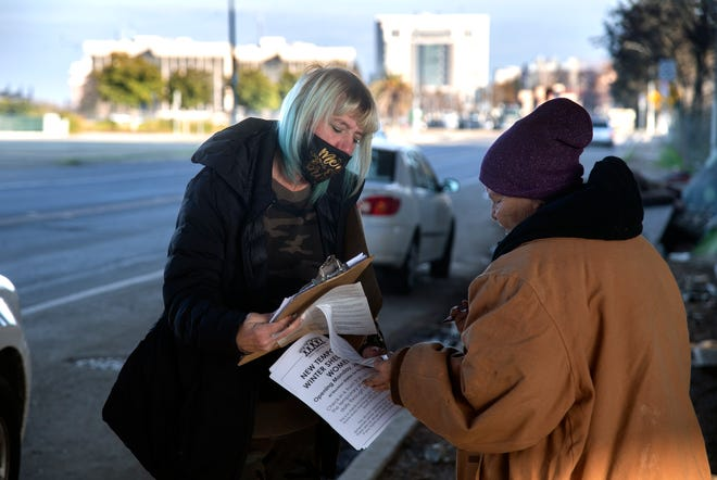 Kathie Trees, who was once homeless herself, left, hands out the Tent 2 Tent newsletter to people at a homeless encampment on Weber Avenue near Washington Street in downtown Stockton. Trees and Kitty Ruhstaller created the newsletter to inform the homeless about programs and services that they can take advantage of.