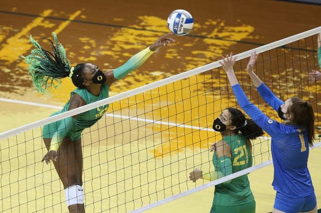 Oregon's Gloria Mutiri, left, tips the ball over the net while Kylie Robinson (21) looks on against UCLA earlier this season in a match at Matthew Knight Arena.
