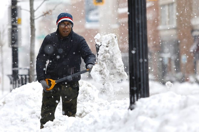 Leonard Mackey, seen on Jan. 31, 2021, in downtown Rockford, shovels after a heavy snowfall. More snow is expected Thursday and Friday.