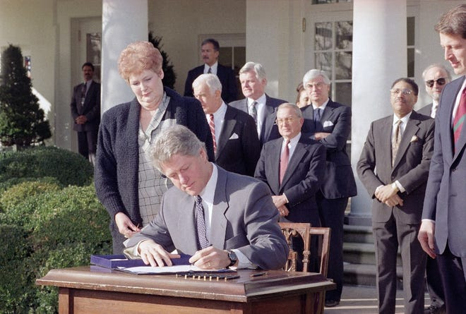 President Clinton signs the Family and Medical Leave Act as Vicki Yandle of Marietta, Georgia, looks on in the Rose Garden of the White House on Feb. 5, 1993. Yandle lost her job when she took time off when her daughter was sick. Behind the president, from left, are: House Speaker Thomas Foley, Sen. Edward M. Kennedy (D-Mass.), Rep. William Ford (D-Mich.), and Sen. Christopher Dodd (D-Conn.) At far right is Vice President Al Gore.