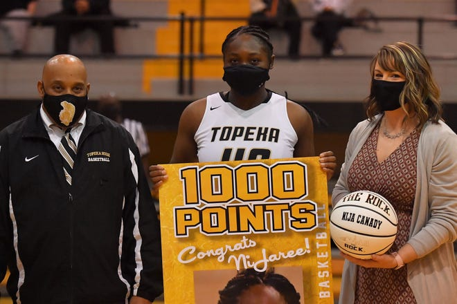 NiJaree Canady holds up a sign paying tribute to reaching the 1,000-point milestone earlier this season. Canady was honored Saturday when the Trojans played Leavenworth.