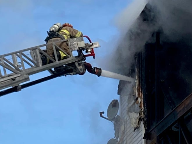 A firefighter battles a fire Sunday at 17 Waters St. in Millbury.