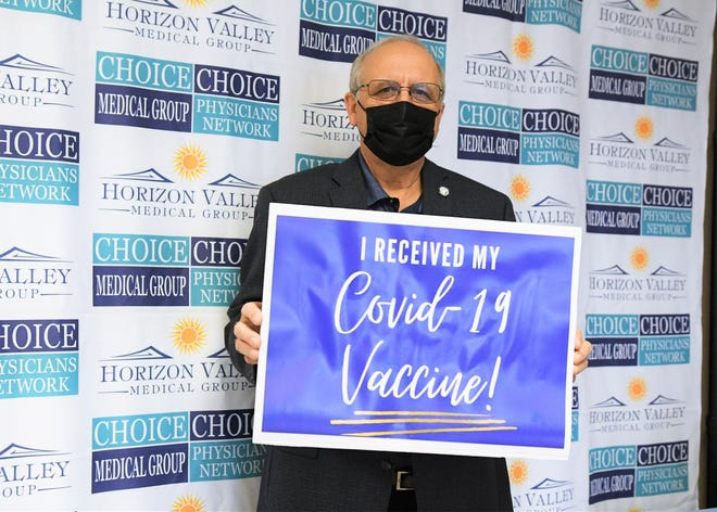 Apple Valley Mayor Curt Emick holds up a sign after receiving a COVID-19 vaccination on Friday, Jan. 29, 2021.