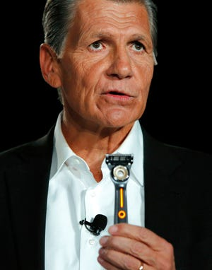 FILE - Procter & Gamble Chief Brand Officer Marc Pritchard holds up the Gillette Heated Razor during a Procter & Gamble news conference, Sunday, Jan. 5, 2020, in Las Vegas. Procter & Gamble's sales were up last year, since it happens to make just about everything people needed while staying at home: Charmin toilet paper, Bounty paper towels and Tide laundry detergent. While Gillette razors sales have slumped Pritchard has talked about people's shaving habits and how P&G is creating products for consumers who are home more. (AP Photo/John Locher, file)