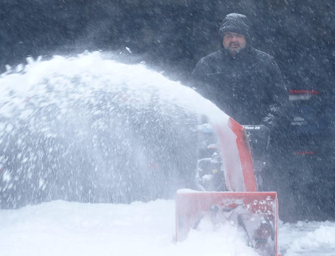 Joel Berman uses a snowblower to clear his driveway Jan. 31 in Bayside, Wisconsin. The area was dumped on with around 10 inches of snow, then lake effect snow added to the accumulation.