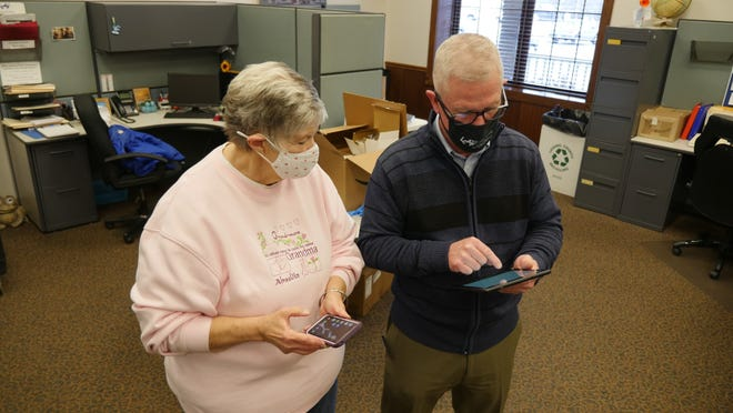 Dave Bibler, Licking County Aging Program executive director, helps Linda Grove of Heath set up her Amazon Fire tablet. LCAP was able to purchase over 100 tablets for county residents 60-and-older through a CARES Act grant.