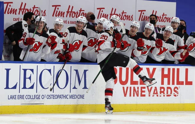 Jan. 31, 2021; Buffalo, N.Y., USA; New Jersey Devils center Michael McLeod (20) celebrates his goal with teammates during the first period against the Buffalo Sabres at KeyBank Center.