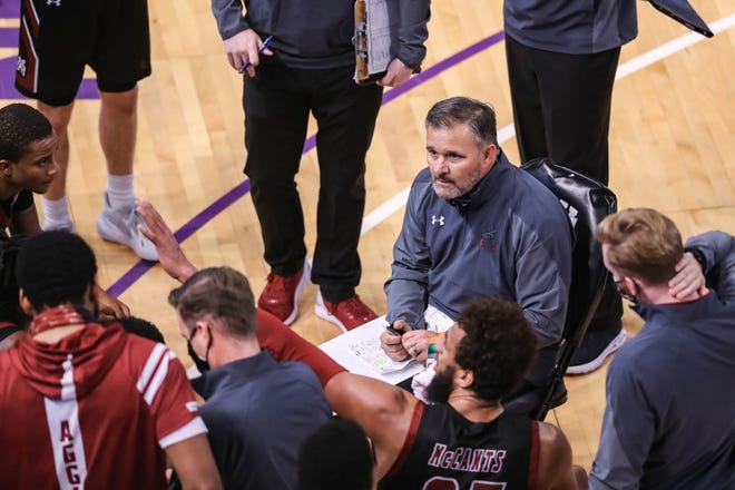 Head coach Chris Jans sits with his players during a timeout as New Mexico State University faces off against Grand Canyon University in Phoenix on Saturday, Jan. 30, 2021.