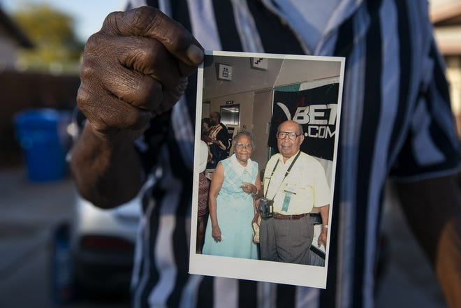 Melvin Juniel holds a photo of his mother, Laura Dungee Harris, and his father, Richard E. Harris, who was the first Black reporter at The Arizona Republic.