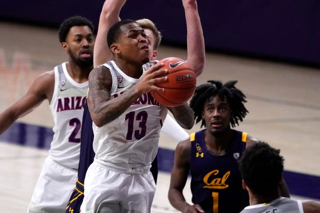 Arizona guard James Akinjo (13) drives past California guard Joel Brown (1) during the first half of an NCAA college basketball game, Saturday, Jan. 30, 2021, in Tucson, Ariz.