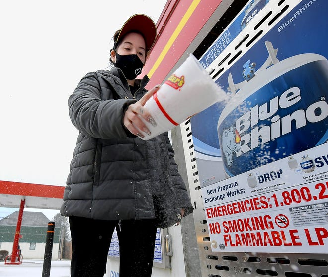 Rutter's employee Katie Smith spreads salt outside the New Freedom convenience store after snow began falling Sunday, Jan. 31, 2021. York County is under a winter storm warning until Tuesday morning. Bill Kalina photo