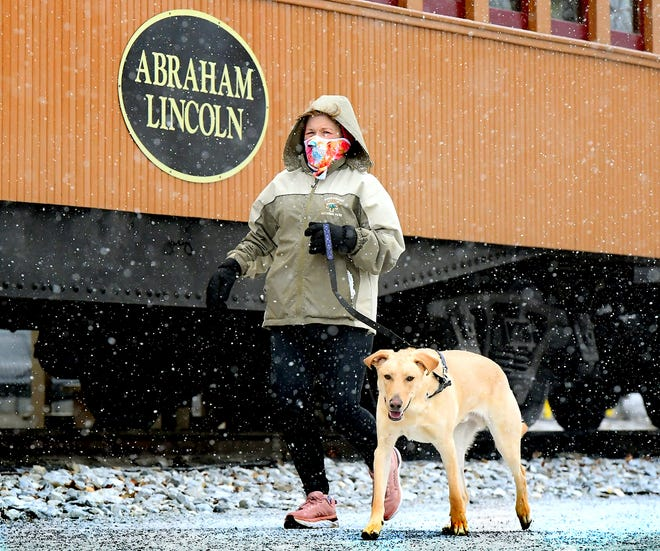 Denise Lessner of New Freedom passes the Northern Central Railway in the borough while running with her dog, Ralphie, during a snow squall Sunday, Jan. 31, 2021. She said she was training for a 20-mile run later this year. York County is under a winter storm warning until Tuesday morning. Bill Kalina photo