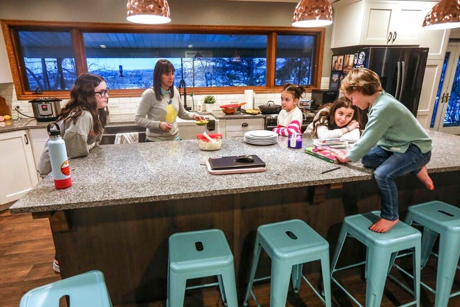 Molly, left, Kim, Mia, Missy and Max Millard gather for dinner in their home in Layton, Utah on Thursday, Jan. 28, 2021. (Annie Barker/The Deseret News via AP)